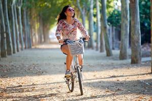 hübsches junges Mädchen, das Fahrrad in einem Wald reitet. foto