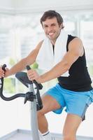 lächelnder Mann, der an der Spinnklasse im hellen Fitnessstudio arbeitet foto