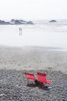 zwei rote Stühle am Strand