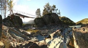 Hängebrücke über den Bergfluss. Abend. Sommerlandschaft. p