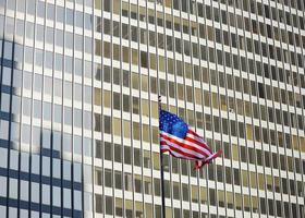 USA-Flagge mit Wolkenkratzer auf Hintergrund