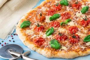 Pizza mit Kirschtomaten und Basilikum foto