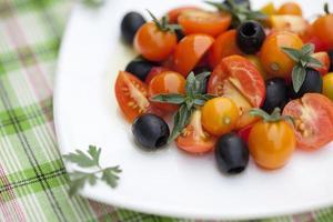 Salat mit Tomaten, Oliven und Basilikum auf einem Teller foto