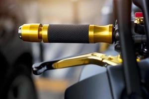 Goldmotorradgriff auf Straßenhintergrund