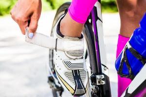 Profi-Radfahrer knöpft Fahrradschuhe am Verschluss foto