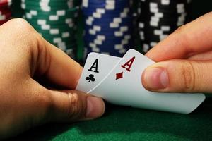 Chips und Karten in Händen auf grünem Tisch foto