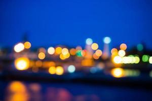 Ansicht der Nachtlichtunschärfe mit Reflexion im Wasser foto