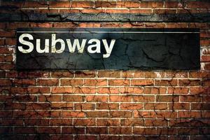 ein rissiges und unglückliches U-Bahn-Schild, das an einer Wand hängt foto