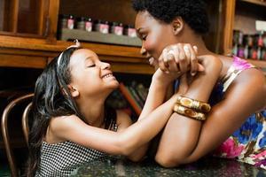 Mutter und Tochter Händchen haltend im Cafe foto