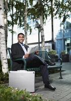 Geschäftsmann, der Zeitung auf Bank liest foto