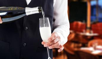 Porträt des Kellners, der Champagner in eine Flöte gießt foto