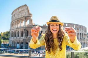 Frau, die Kopfhörer mit Audioguide nahe Kolosseum in Rom gibt foto