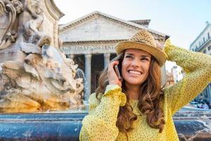 glückliche Frau, die auf Handy am Pantheonbrunnen plaudert