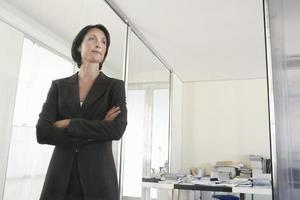 Geschäftsfrau stehen im Büro verschränkte Arme foto