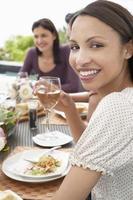 Frau hält Weinglas bei Dinnerparty