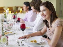 Frau sitzt mit Freunden bei der Dinnerparty