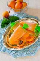 Pfirsicheis auf einem weißen hölzernen Hintergrund foto