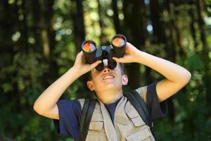 Junge im Wald, der durch Fernglas schaut foto