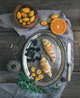 Rustikales Frühstücksset: Schokoladencroissants auf Metallschale, frisch foto