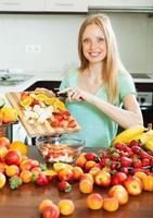 glückliche blonde Frau, die Früchte schneidet foto