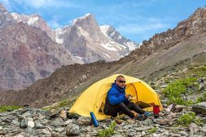 kühler Mann, der Mittagessen in der Bergwanderung isst foto