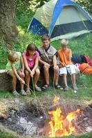 Kinder auf dem Campingplatz braten Marshmallows foto