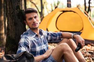 Mann, der nahe Zelt im Wald ruht foto