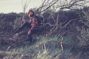 Mann mit Rucksack sitzt auf umgestürztem Baum foto