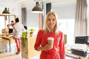 glückliche kreative Frau mit Kaffeetasse im Büro