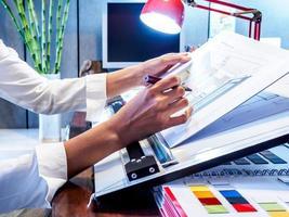 Innenarchitektenhand, die mit Illustrationsskizze auf Schreibtisch arbeitet foto