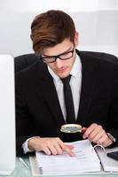 Geschäftsmann, der Dokument analysiert foto