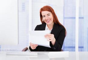 glückliche Geschäftsfrau, die Dokument hält foto