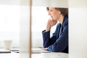 Geschäftsfrau sitzt beim Lesen eines Dokuments foto