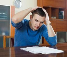 Mann füllt Finanzdokumente aus foto