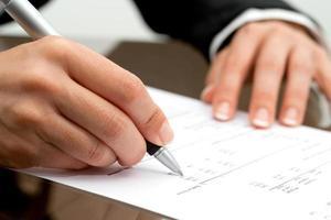 weibliche Hand mit Stift, der auf Buchhaltungsdokument zeigt. foto