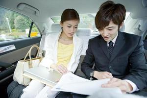 Mann und Frau betrachten Dokumente im Taxi foto