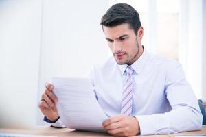 Geschäftsmann, der am Tisch sitzt und Dokument liest foto