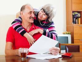 fröhlicher reifer Mann mit Frau, die Finanzdokumente liest foto