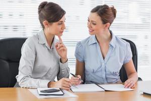 lächelnde Geschäftsfrauen, die zusammen an Dokumenten arbeiten
