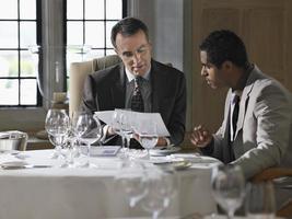 Geschäftsleute, die Dokumente am Restauranttisch analysieren foto