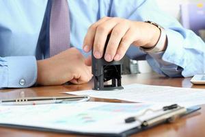 Nahaufnahme der Geschäftsmannhand, die einen Stempel auf Dokument drückt foto