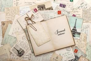 offenes leeres Tagebuch, alte Briefe, französische Postkarten foto
