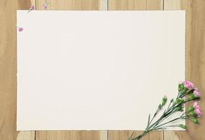 leeres weißes Papier und rosa Nelke auf hölzernem Hintergrund foto