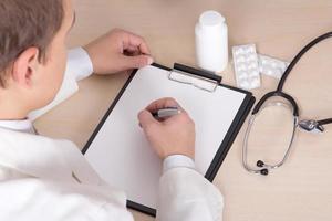 männlicher Arzt verschreibt Behandlung in modernen Büro foto
