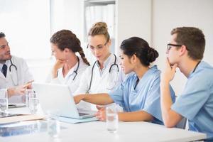 Arzt und Krankenschwester diskutieren über Laptop foto