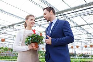 positiver Geschäftsmann, der Geschäft mit seinem Floristen bespricht