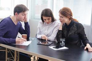 Drei Geschäftsleute diskutieren gemeinsam etwas foto
