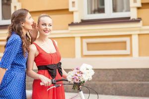 fröhliche junge Freundinnen gehen in der Stadt spazieren foto