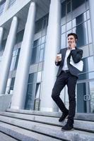 Der hübsche junge Geschäftsmann geht aus seinem Büro foto