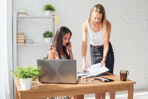 Geschäftsfrau spricht und zeigt etwas im Kollegen im Büro foto